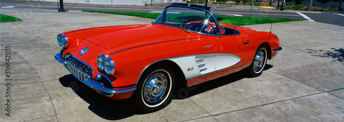 This is a restored 1959 Corvette. It is bright red with a white side panel with white sidewall tires. The convertible top is down. It is parked on flat pavement. - 316642031