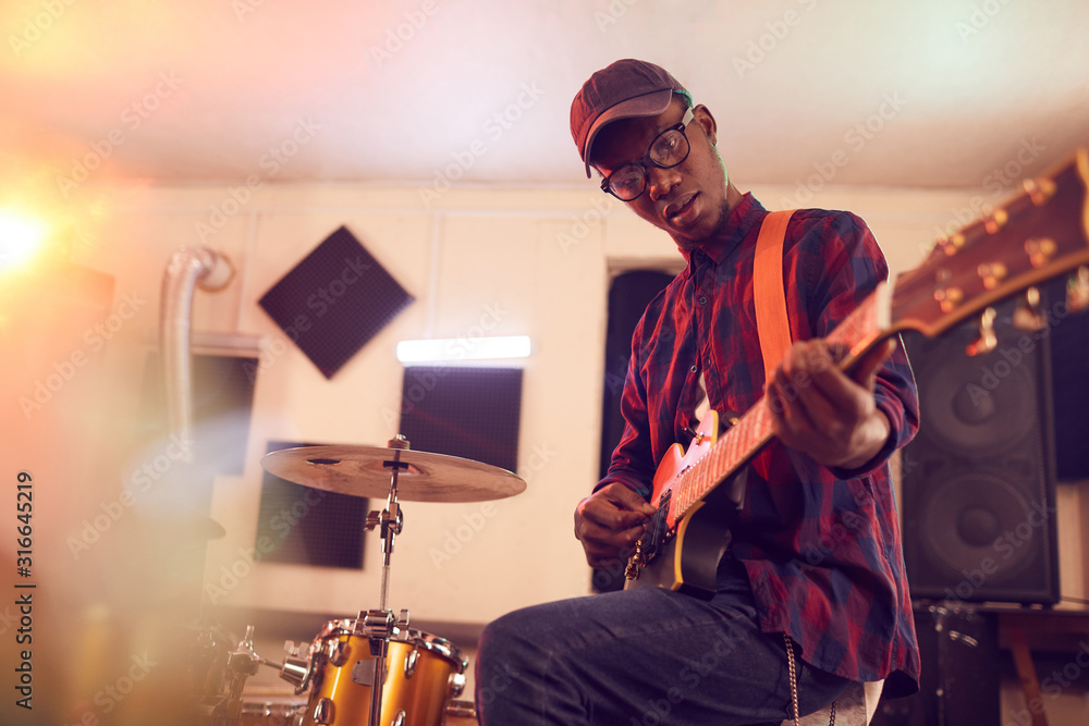 Fototapeta Low angle portrait of contemporary African-American man playing guitar and looking at camera during rehearsal or concert with music band in studio, copy space