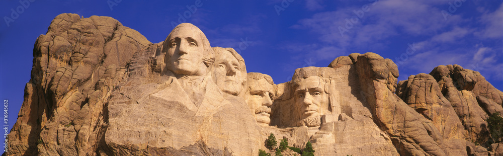 Fototapeta This is a close up view of Mount Rushmore National Monument against a blue sky. It shows the four faces of George Washington, Thomas Jefferson, Theodore Roosevelt, and Abraham Lincoln.