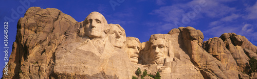 This is a close up view of Mount Rushmore National Monument against a blue sky Fotobehang