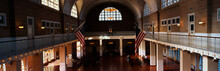 This Is The Interior Of The Great Hall At Ellis Island Which Signifies Immigration To The United States.  There Are Two American Flags Flying Posted At The Center Of The Walls.