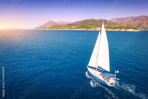 Foto Aerial view of beautiful white sailboat in blue sea at bright sunny summer evening
