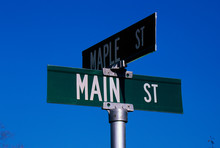 This Is A Street Sign Labeling The Corner Of Main Street & Maple Street. The Sign Is Green With White Lettering Against A Blue Sky.