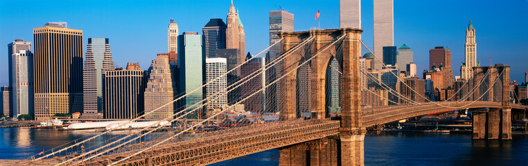This is a close up of the Brooklyn Bridge over the East River. The Manhattan skyline is behind it at sunrise.