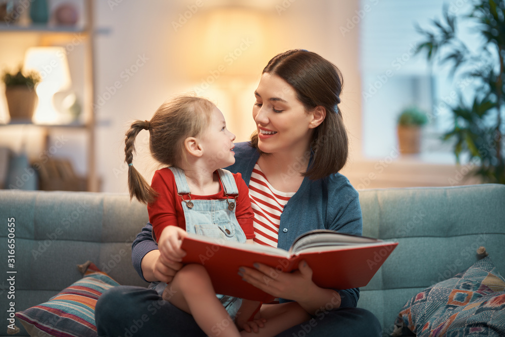 Fototapeta mother reading a book to daughter