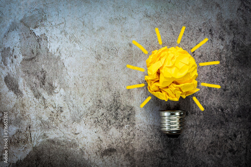 Obraz Great idea concept with crumpled yellow paper light bulb isolated on dark background - fototapety do salonu