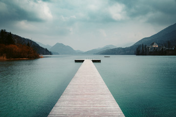 Wooden landing stage with alpine lake in summer