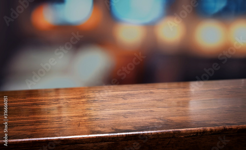 Fototapeta nightclub background.Empty diagonal brown wooden table with blur bar restaurant bokeh lights,banner mockup template for display of product obraz