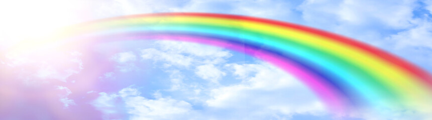 The rainbow background that appears in the sky and the sky is bright, with the light of the sun shining against the white clouds as a beautiful background.