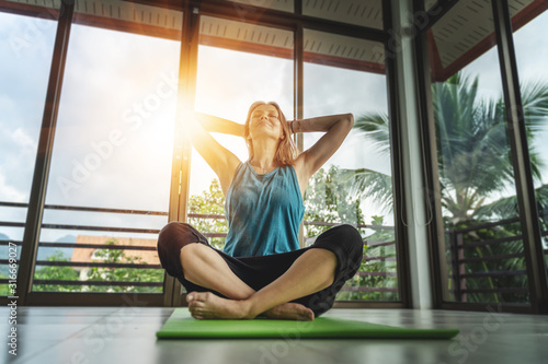 Carta da parati  An attractive 40-year-old middle-aged woman practices yoga in a panoramic window room overlooking the garden at dawn in the sunshine