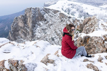 Beautiful European Girl In A Red Park, Warm Jacket, Jeans, Black Leather Boots And Sunglasses Sits On Top Of A Snowy Mountain And Looks Into The Distance