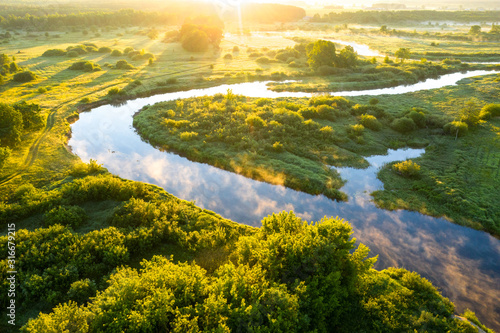 Obraz Summer morning on the river with fog, aerial view. River located between forest and green fields - fototapety do salonu
