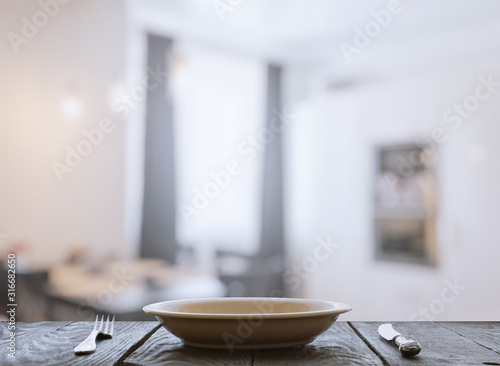 Fototapeta empty plate with fork and knife on wooden table obraz