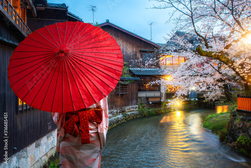 Asian young woman traveller wearing japanese traditional kimono with red umbrella sightseeing at famous destination cherry blossom at Shirakawa River in the Gion District at night in Kyoto, Japan Tableau sur Toile
