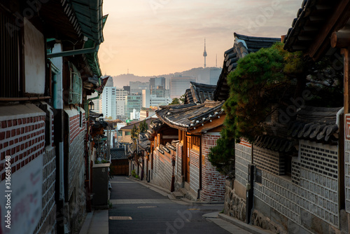 Traditional Korean style architecture at Bukchon Hanok Village with N Seoul Tower in background in Seoul, South Korea Canvas Print