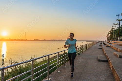 Woman running on street with a view of river in the morning. Fototapete