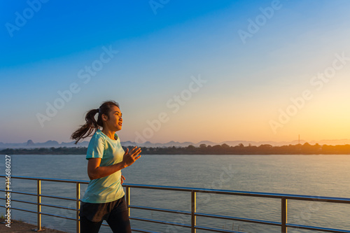 Foto  Woman running on street with a view of river in the morning.