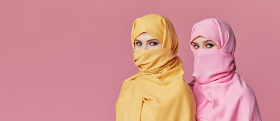 Girl power. Two young Muslim arabian women wearing colorful hijabs against pink background. Points finger to side. Space for text