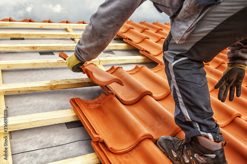 Carta da parati Roofer at work, installing clay roof tiles, Germany