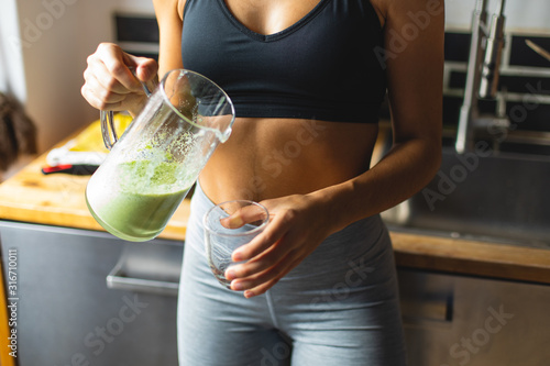 Fototapeta Fitness diet concept. Sporty woman drinking a green detox smoothie for breakfast in the kitchen. obraz