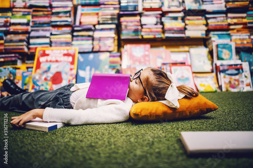 Charming caucasian little blond girl with ponytail lying on the floor in bookstore with book on chest and sleeping Tableau sur Toile