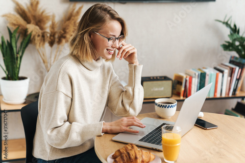 Tela Photo of caucasian woman using laptop while having breakfast at home