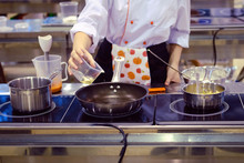 A Woman Cook Pours Oil Into A Frying Pan In The Kitchen In A Cafe