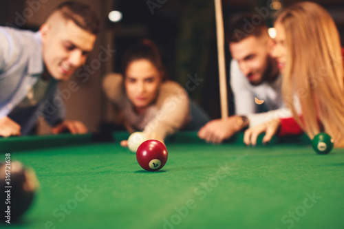 Foto Group of friends play billiards at night out