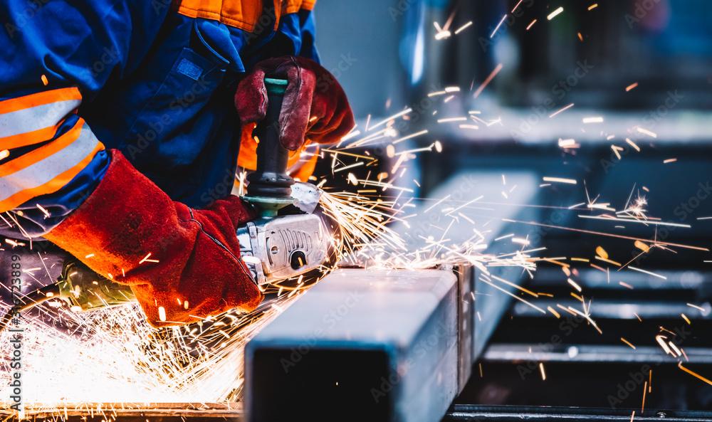 Fototapeta Worker grinding in a workshop. Heavy industry factory