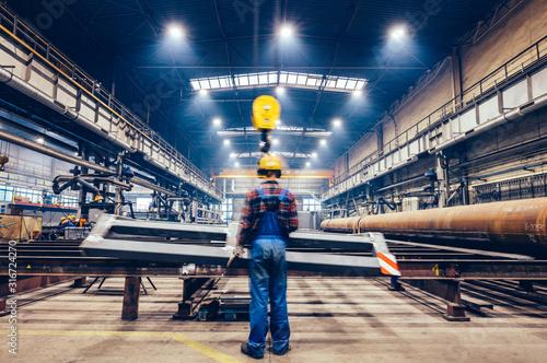 Платно Blue-collar worker operating crane hook in a big factory.