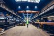 Leinwanddruck Bild - Engineer walking in large factory, blue-collar workers at work.