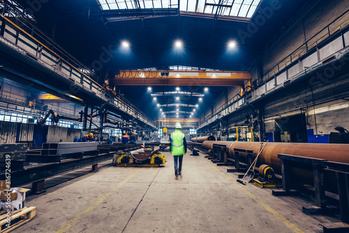 Engineer walking in large factory, blue-collar workers at work.