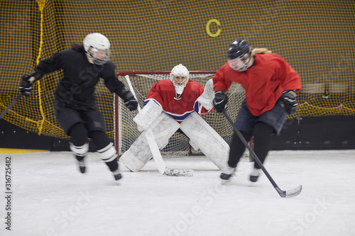 Cuadros en Lienzo Full length action shot of female hockey team fighting during match, copy space