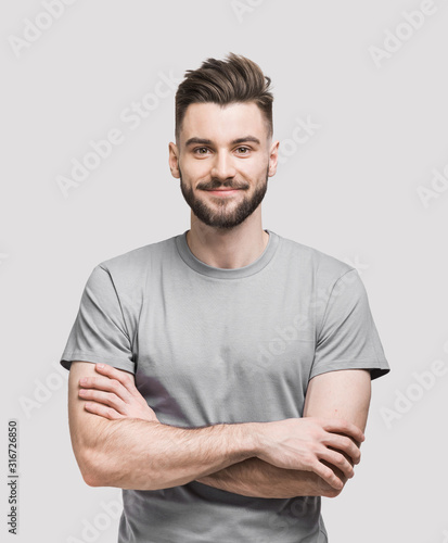 Obraz Portrait of handsome smiling young man with folded arms. Smiling joyful cheerful men with crossed hands studio shot. Isolated on gray background - fototapety do salonu