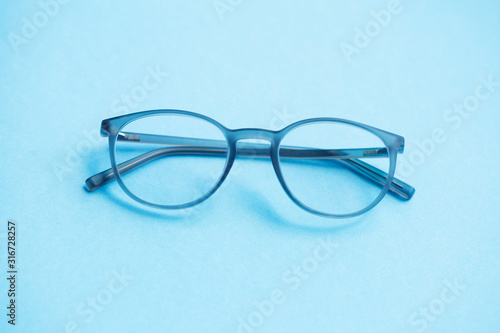 eyeglasses isolated on blue background Wallpaper Mural