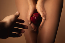 Cropped View Of Man Reaching Woman In Nylon Tights Holding Ripe Red Apple Isolated On Brown