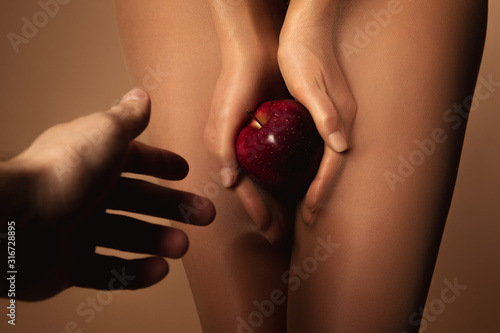 cropped view of man reaching woman in nylon tights holding ripe red apple isolated on brown - 316728895