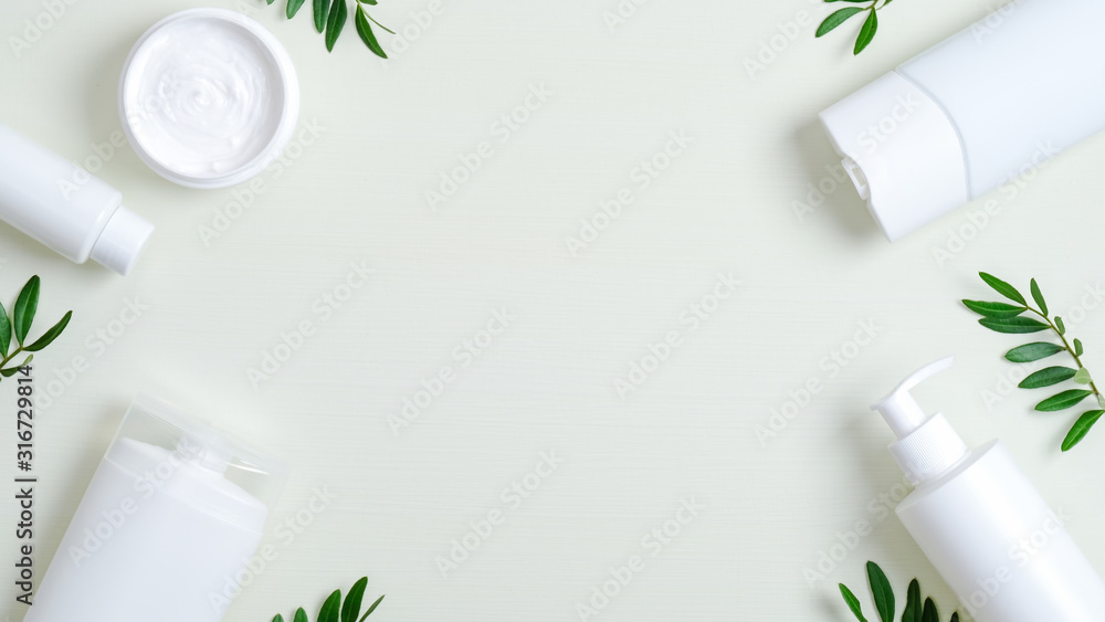 Fototapeta Frame of natural cosmetic products and green leaves. Top view hand cream, shampoo bottle, shower gel, hair lotion. Organic cosmetic, SPA treatment concept. Banner mockup for beauty salon