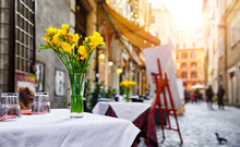 Rome Italy. Street Near Trevi Fountain. Picturesque Landscape Old Town With Restaurants, Shop-window Shop, Table Cafe With Bunch Flower.