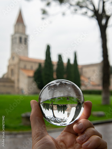 Photo The cathedral of Aquileia through glass sphere on a cloudy day in late autumn