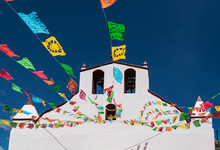 Upward Perspective On A Small White Church In Rural Chiapas, Mexico, With Colorful Flags Against Deep Blue Sky Backdrop.