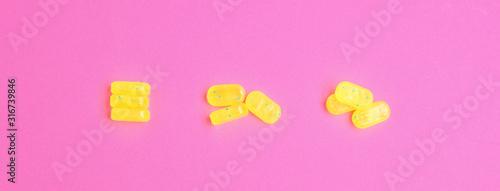 Tasty lemon drops on pink background, flat lay