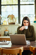 Attractive caucasian brunette in sweater sitting in cafe and drinking coffee. In front of her is laptop.