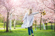 Leinwandbild Motiv Young woman enjoying the nature in spring. Dancing, running and whirling in beautiful park with cherry trees in bloom. Happiness concept