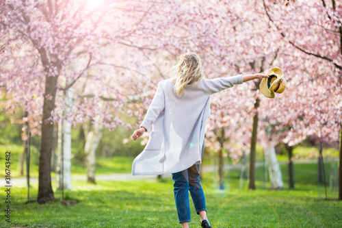 Obraz Young woman enjoying the nature in spring. Dancing, running and whirling in beautiful park with cherry trees in bloom. Happiness concept - fototapety do salonu