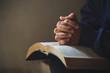 Leinwandbild Motiv Hands folded in prayer on a Holy Bible in church concept for faith