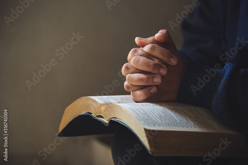 Obraz na plátně Hands folded in prayer on a Holy Bible in church concept for faith