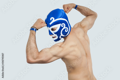 Obraz Rear view of a shirtless man in wrestling mask flexing muscles over gray background - fototapety do salonu
