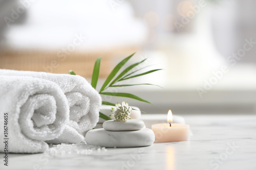 Obraz Beautiful composition with spa stones on white marble table - fototapety do salonu