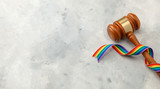 Fototapeta Tęcza - Judge gavel and rainbow ribbon of LGBT pride on gray background. Copy space for text